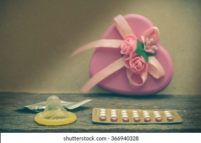 Condom and contraceptive pills on wood table