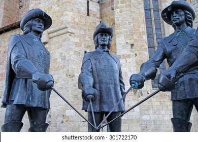 CONDOM, FRANCE, June 24, 2015 : The statue of d'Artagnan and three musketeers, from the Georgian sculptor Zurab Tsereteli, lies at the foot of the Cathedral