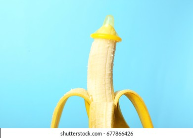 Condom on banana against color background. Safe sex concept