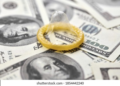 Condom on dollars bills. Prostitution concept. US dollar money on table with contraceptive. Pay for sex per night. Harlotry and whoredom.