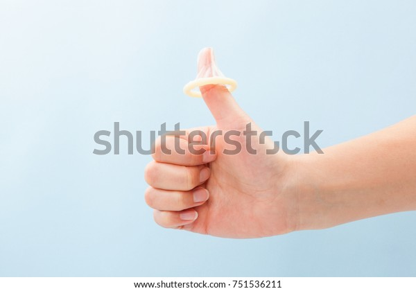 Condom on thumb up gesture. Female hand with thums up and condom on thumb. Safe sex concept.