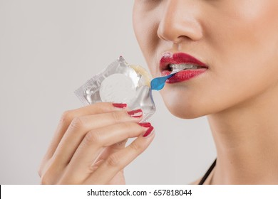 The condom is shown by women,Condom in the hands of women,Open mouth and sexy lips,Remember about protection,Safe sex concept.Contraceptive,birth control.
