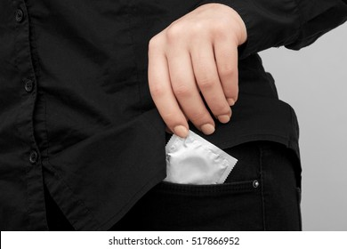 Condom silver color. Woman is holding a condom. Cropped image of girl in jeans putting a condom into pocket, against dark background.