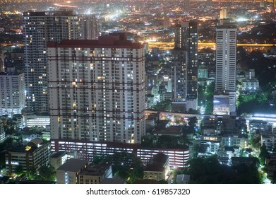 Condominium and skyscrapers with downtown night scene on city scape at night in Bangkok Thailand.