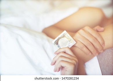 Condoms ready to use in young male and woman hand holding on the bed, give condom safe sex concept  Prevent infection and Contraceptives control the birth rate or safe prophylactic. World AIDS Day