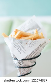 a cone of french fries in fake newspaper