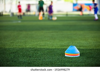 Cone markers is soccer training equipment on green artificial turf with blurry kid players training background. Material for training class of football academy.