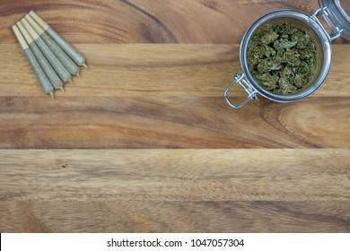 Cone shaped joints with weed nugs in a glass jar on a wood surface