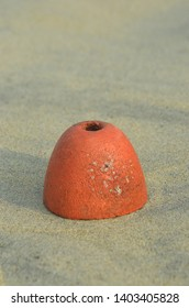 A cone shaped orange bouy rests on some pale sand on a beach in Vietnam. A hole is in the top of the bouy. It casts a shadow onto the sand.
