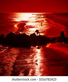 Coney Island Beach in New York City. Silhouettes of peoples on rocks on the ocean coast on a sunset background