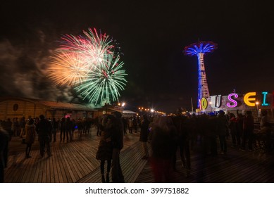 CONEY ISLAND, BROOKLYN, NY/USA -  JANUARY 1, 2016: Revelers ring in the new year on the Coney Island boardwalk with fireworks and a lighting display on the historic Parachute Jump.
