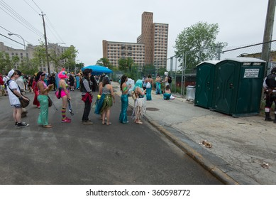 CONEY ISLAND, BROOKLYN, NY/USA - JUNE 20, 2015: Costumed participants wait to use the restroom before the annual Mermaid Parade.