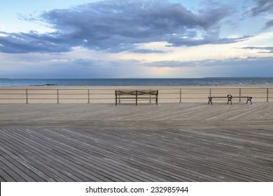 Coney Island empty boardwalk with bench, Brighton beach, Brooklyn, New York