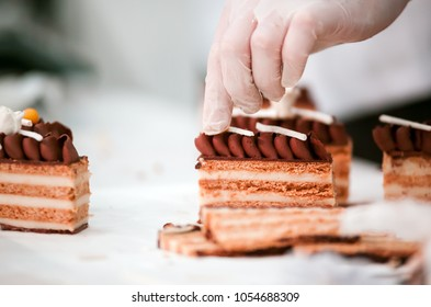 Confectioner decorating cake in pastry shop, confectionery industry