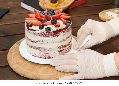 Confectioner, with gloves, putting the finishing touches on the Red Velvet cake. In the background turron and brigadiers (traditional Brazilian sweet).