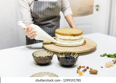 Confectioner with pastry bag squeezing cream on cake at kitchen. The concept of homemade pastry, cooking cakes.