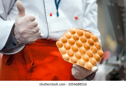 Confectioner presenting bubble waffle in pastry shop