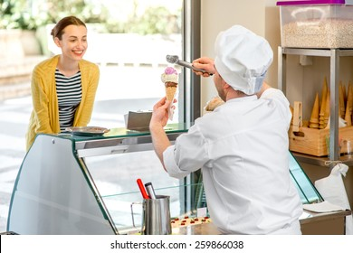 Confectioner selling ice cream to young woman in the pastry shop