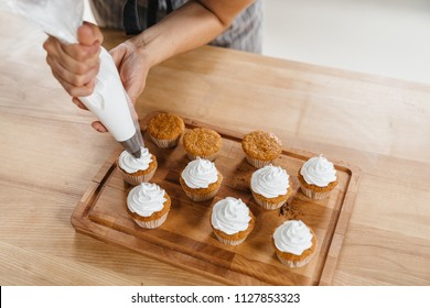 Confectioner woman decorates a capcake or muffin with whipped cream through a pastry bag.