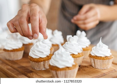 Confectioner woman decorates traditional capcakes and muffins with marshmallow slices.