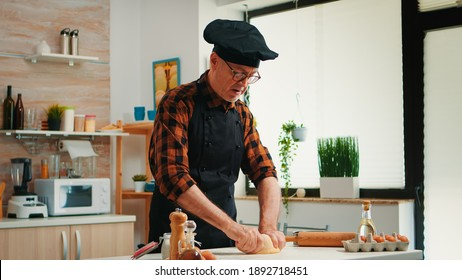 Confectioner working at home with raw dough in modern kitchen recording the recipe. Retired elderly baker with bonete mixing ingredients with sifted flour kneading for baking traditional bread.
