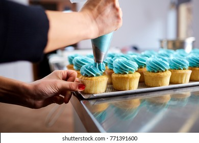 The confectioner's hands are decorated with a cream of pipping b