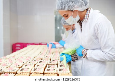 Confectioners in white uniform and gloves decorating small cakes in pastry factory