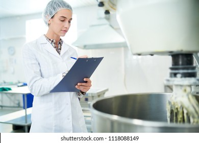 Confectionery factory employee standing in white coat near operating machinery and making notes.