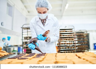 Confectionery factory employee in white coat squeezing chocolate cream from pastry bag.