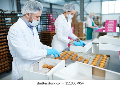 Confectionery factory employees in white coats collecting freshly baked pastry from tray and putting it into paper boxes.