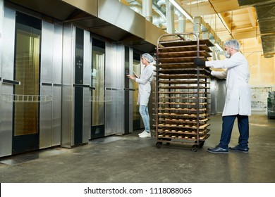 Confectionery factory employees in white coats waiting for elevator to transport trays rack with pastry.