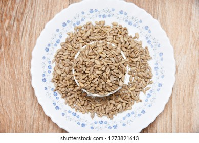Confectionery sunflower seeds used as food, United Kingdom. dehulled kernel in wooden texture background. eaten as a snack or as part of a meal, garnishes or ingredients in various recipes.