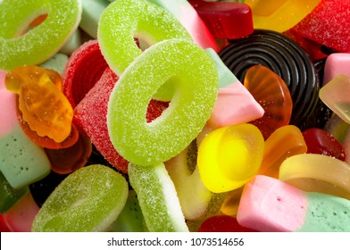 confectionery sweets and assorted lollies concept with close up of an assortment of gummy, colorful and chewy candy with sprinkled sugar