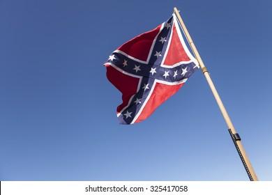 Confederate Flag on pole over blue sky.