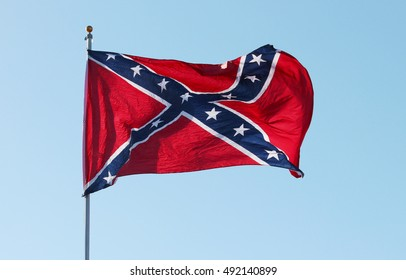 Confederate rebel flag waving in the wind against the blue sky background in Charleston, South Carolina, USA.