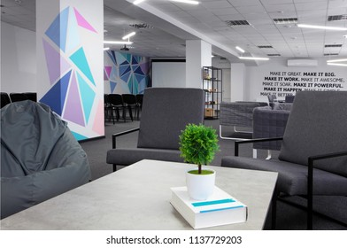 Conference hall.Coffe table with green plant and armchair on the first plan .Office. With motivation words on the wall