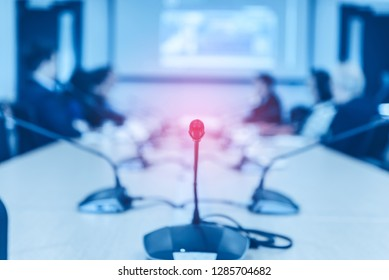 Conference microphones on the table over abstract blurred of attendee in meeting room background