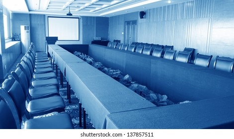 Conference room with empty chairs and a projector screen