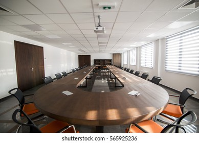 Conference room interior with empty chairs and a projector screen
