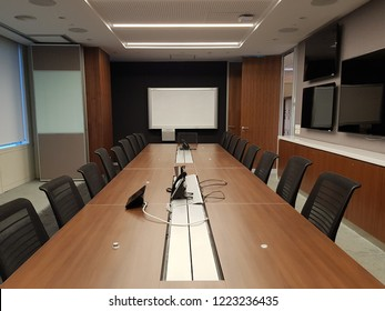 Conference room with long table, chairs, whiteboard,  LCD screens and speakerphone in a corporate office