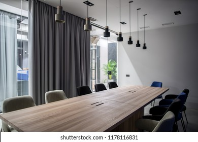 Conference room in a luminous office with gray walls. There are wide wooden tables with multicolor chairs, glass partition with a door and curtain, different lamps, green plants. Horizontal.