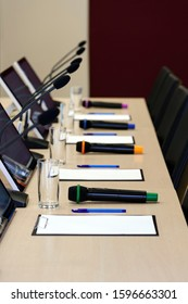 Conference room table for business meeting with microphones, monitors, pens, papers, glasses for water and chairs in row, selective focus