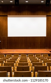 Conference room with wooden seating, stage and large cinema screen in auditorium. Wooden room for conferences and shows, cinema and theater. Big white screen in the background