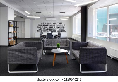 Conference room.With coffe table and armchair on first plan and conference , meeting table and office armchair. With motivation words on the wall