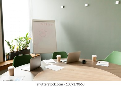 Conference table with laptops and chairs in empty meeting room with nobody, modern company office boardroom interior with flip chart for daily work and corporate team group business briefings concept