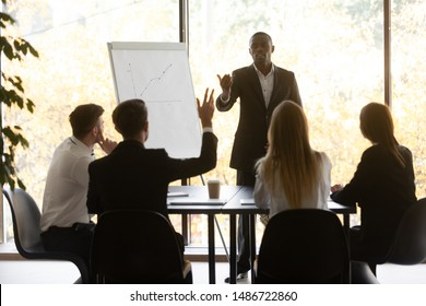 Conference training male participant raise hand ask african speaker presenter question at diverse group corporate meeting showing initiative at team workshop, knowledge and business education concept