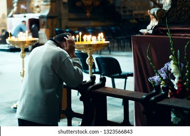 the confession (prayer, humbling) of the man standing on his knees, shakes his face with his hands, in the church