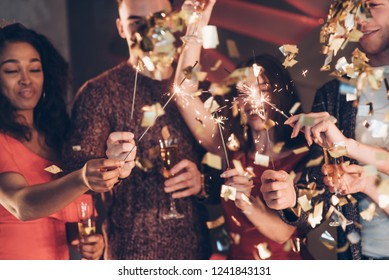Confetti in the air. Multiracial friends celebrate new year and holding bengal lights and glasses with drink.