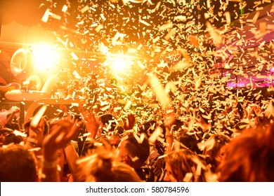 Confetti fired in the air during a in a disco. Hundreds of hands to the sky. Orange tone/background