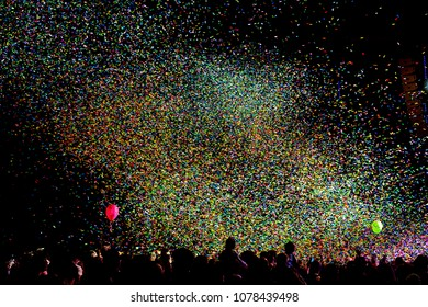 Confetti fired on air on dancefloor during a festival at night. People are happy and with hands in the air. Image ideal for backgrounds. Multicolor are the confetti in the picture.Silhouette of people
